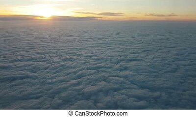 Aerial shot of rough clouds from aircraft window at splendid sunset in summer