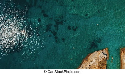 Aerial shot of sea waves and cliff. Sveti Nikola Island rock...