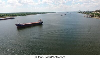 Aerial shot of several barges floating in the Dnipro river on a sunny day
