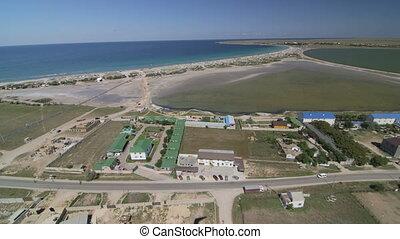 Aerial shot of shoreline and township. Olenevka, Tarhankut,...