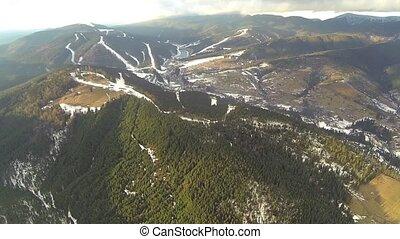 Aerial shot of ski resort Bukovel with snow covered slopes at spring