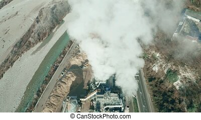 Aerial shot of smoking pipes of a small plant in the river...