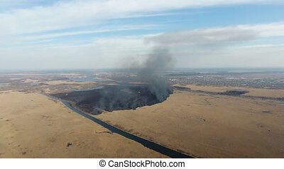 Aerial shot of smoking sedge and reed marshes between two inflows in spring