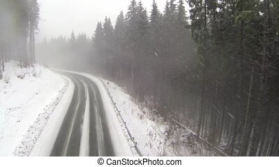 Aerial shot of snow-covered road in the countryside Carpathian Mountains.