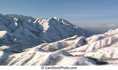 aerial shot of snowy mountains with Salt Lake Valley in the distance