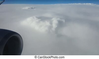 Aerial shot of snowy white clouds from an aircraft window in summer