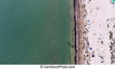 Impressive bird`s eye view of a Black Sea coastline with straight beach, white sand, sunshades, weeds, relaxing tourists in summer. It looks cheerful and touristic.