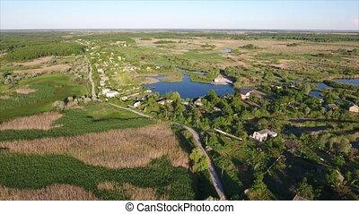 Aerial shot of summer cottages, splendidl lake and reedbeds in Ukraine in summer