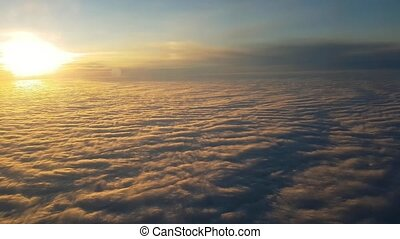 Aerial shot of surrealistic clouds from flying aircraft at sunset in summer