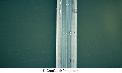 Aerial shot of the cable bridge with pedestrians, bicycles and cars crossing the river, top view. 4K clip