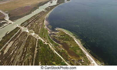Aerial shot of the curvy seacoast of Dzharylhach island,...