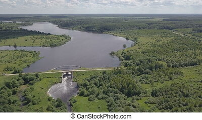 Aerial shot of the dam. The wide river becomes narrow....