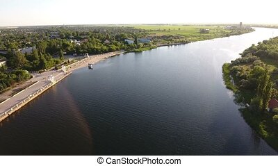 Aerial shot of the Dnipro quay with an asphalted road and greenary at sunset