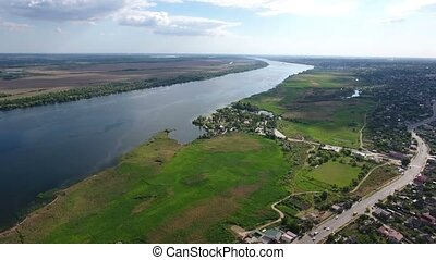 Aerial shot of the Dnipro river a country road stretching nearby in a sunny day