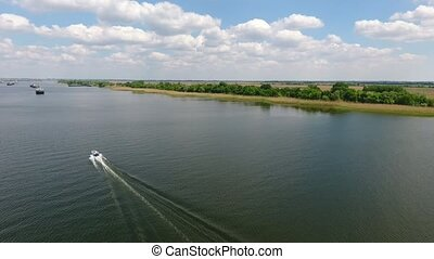 Aerial shot of the Dnipro river and a small motorboat...