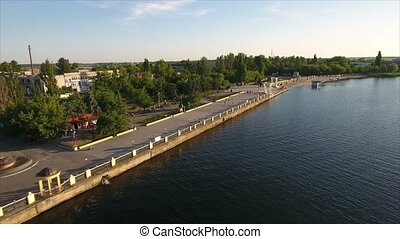 Aerial shot of the Dnipro river and its modern embankment covered with greenary