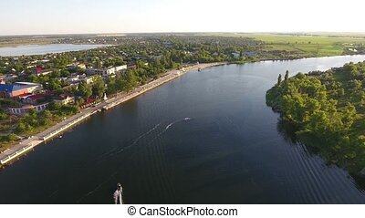Aerial shot of the Dnipro river and its riverbanks covered with houses and trees