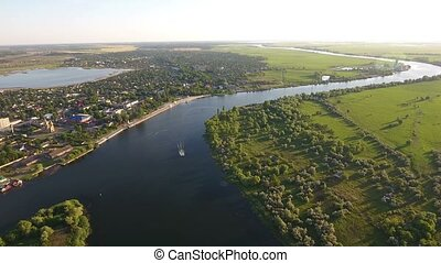 Aerial shot of the Dnipro river banks with roads, houses and greenery in summer