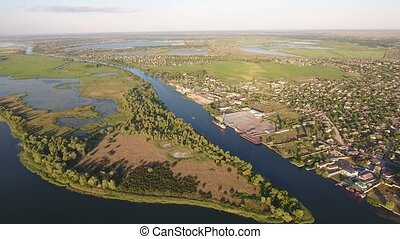 Aerial shot of the Dnipro river banks with trees, roads, houses and greenery
