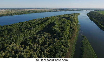 Aerial shot of the Dnipro river basin with rows of wild trees, an islet, inflows