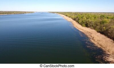 Aerial shot of the Dnipro river bright waters and its riverbank with dry cane