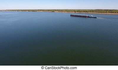 Aerial shot of the Dnipro river calm waters and a slowly moving barge in spring