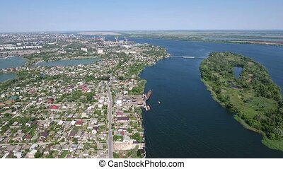 Aerial shot of the Dnipro river embankment with private houses in a sunny day