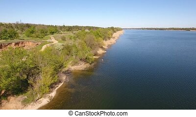 Aerial shot of the Dnipro river sparkling waters and its riverbank with dry cane