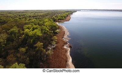 Aerial shot of the Dnipro river coastline with green forest patches on it