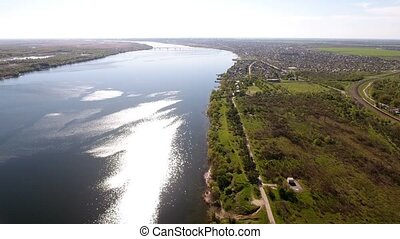 Aerial shot of the Dnipro river coastilne with rugged bank and greenary in spring