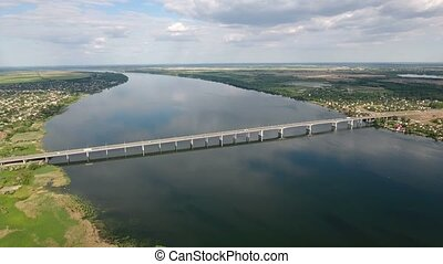Aerial shot of the Dnipro river embankment in Kherson and a car bridge in summer
