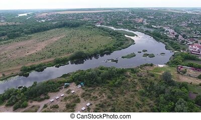Aerial shot of the Dnipro river with calm waters, wetland and cottages in summer