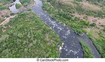 Aerial shot of the Dnipro river with foamy rapids and lush...