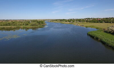 Aerial shot of the Dnipro river with its flourishing greenary and blue waters
