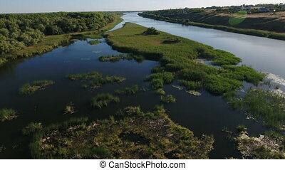 Aerial shot of the Dnipro river with its greenary, wetland, and dark blue waters