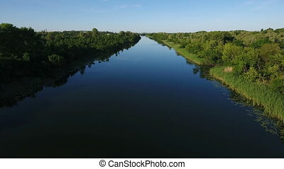 Aerial shot of the Dnipro river with its wild greenary and dark blue waters