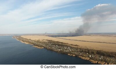 Aerial shot of the Dnipro riverbank and flaming cane patches...
