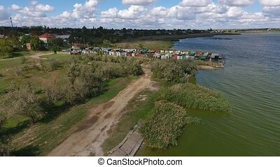 Aerial shot of the Dnipro riverbank with parking for motorboats in summer