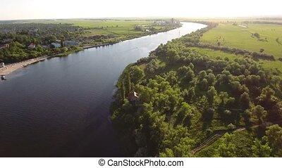 Aerial shot of the Dnipro riverbanks with an asphalted quay and greenary at sunset