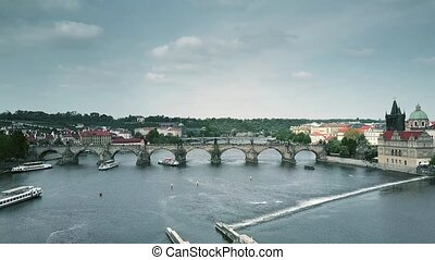 Aerial shot of the famous Charles bridge and the Vltava river tour boats in Prague