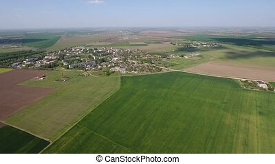 Aerial shot of the fertile green fields in Eastern Europe in late spring