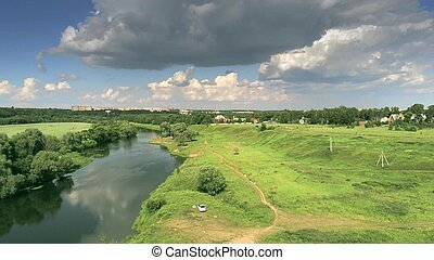 Aerial shot of the Moskva River near Zvenigorod and a village on a partially cloudy summer day
