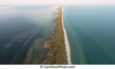 Aerial shot of the narrow and long sand spit covered with...