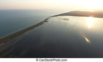 Aerial shot of the narrow land spit covered with bulrush and weeds at sunset