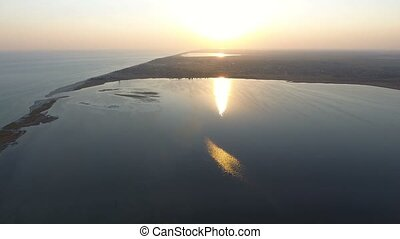 Aerial shot of the narrow snake looking sand spit in the Black Sea at sunset