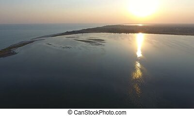 Aerial shot of the narrow spit covered with bulrush and weeds at sunset