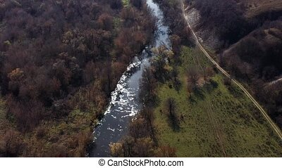 Aerial shot of the Oskol river and many trees in warm sunny weather in Dvurechansky park, Kharkov region, Ukraine. Top view of a transparent clean river with the flow. Beautiful nature without people.