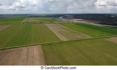 Aerial shot of the plowed fields near the Dnipro river with...
