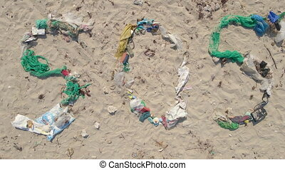 Aerial shot of the sign SOS made of trash on a beach. Ecologic disaster concept. Plastic pollution concept