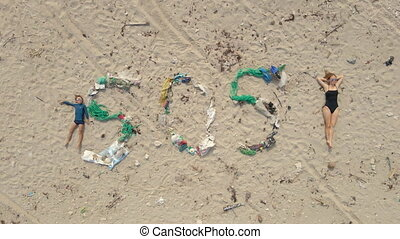 Aerial shot of the sign SOS made of trash on a beach. Woman lays by the sign simbolizing an exclamation mark. Ecologic disaster concept. Plastic pollution concept